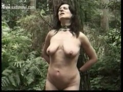 Slave tied to a tree is hit with a whip and master mastrubat.