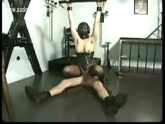 Slave wearing mask sucks cock while other master hits her ti.